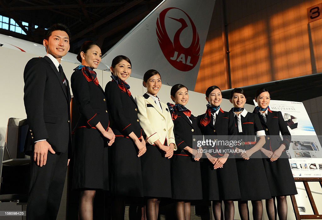 Japan Arilines cabin attendants pose in their new uniforms during a photo session during the company's press preview in their maintenance centre at the Tokyo International Airport in Tokyo on December 20, 2012. JAL displayed their new uniforms and new 'JAL SKY SUIT 777' seats for all cabin categories of their new Boeing 777-300ER jetliners during the press preview.