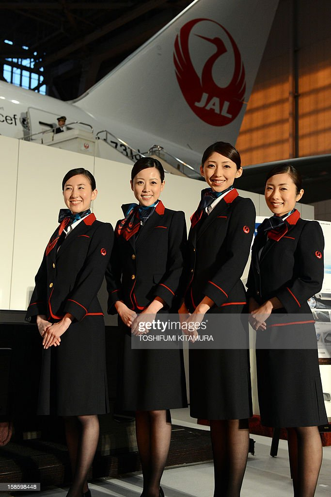 Japan Arilines cabin attendants pose in their new uniforms during a photo session during the company's press preview in their maintenance centre at the Tokyo International Airport in Tokyo on December 20, 2012. JAL displayed their new uniforms and new 'JAL SKY SUIT 777' seats for all cabin categories of their new Boeing 777-300ER jetliners during the press preview. AFP PHOTO / TOSHIFUMI KITAMURA