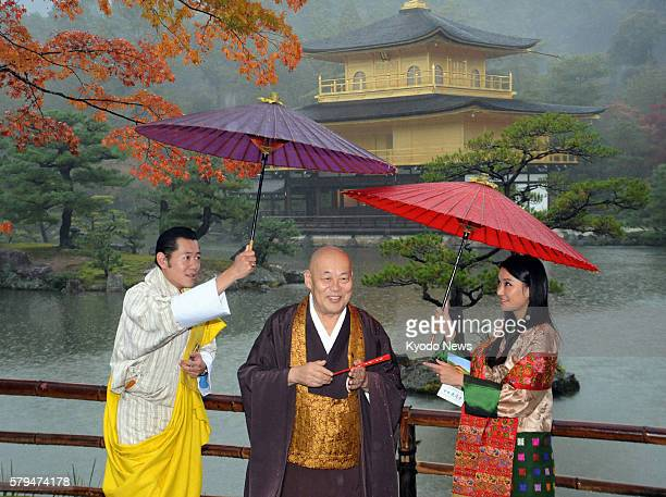 KYOTO Japan Bhutan's King Jigme Khesar Namgyel Wangchuck and Queen Jetsun Pema lean their umbrellas toward Kinkakuji temple master Raitei Arima when...