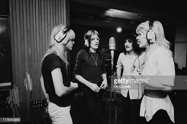 Japan bassist Mick Karn drummer Steve Jansen guitarist Rob Dean and singer David Sylvian British New Wave band wearing headphones and grouped around...