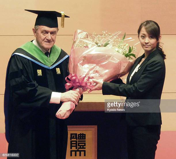 TOKYO Japan Bruno Grandi of Italy president of the International Federation of Gymnastics receives a bouquet from Japanese gymnast Rie Tanaka during...