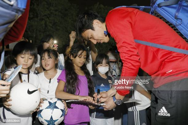 Japan captain Makoto Hasebe signs autographs for children in Al Ain on March 20 2017 Hasebe will fly home from the United Arab Emirates for further...