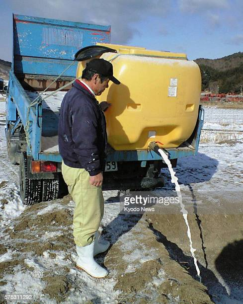 IITATE Japan Cattle farmer Kenichi Hasegawa disposes of breast milk he just expressed from his cows on March 27 in his farm in the village of Iitate...