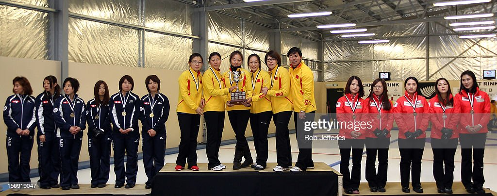 Japan (Silver), China (Gold) and Korea (Bronze) pose for a photo during the Pacific Asia 2012 Curling Championship at the Naseby Indoor Curling Arena on November 25, 2012 in Naseby, New Zealand.