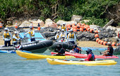 Japan Coast Guard officers haul in a protester from a canoe off the Henoko district of Nago that is the site for relocating the Futenma military base...