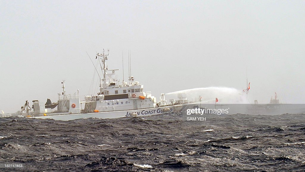 A Japan Coast Guard vessel sprays a water cannon toward a Taiwan fishing boat as they try to sail toward the disputed Diaoyu / Senkaku islands in...