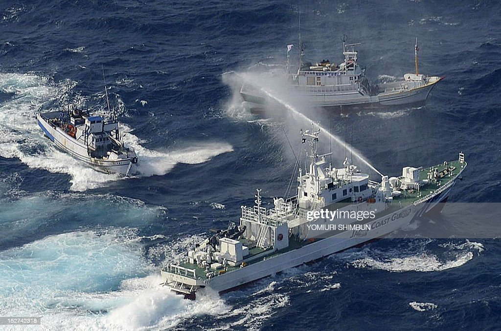 A Japan Coast Guard vessel sprays water against Taiwanese fishing boats in the East China Sea near the Senkaku islands as known in Japanese or Diaoyu...