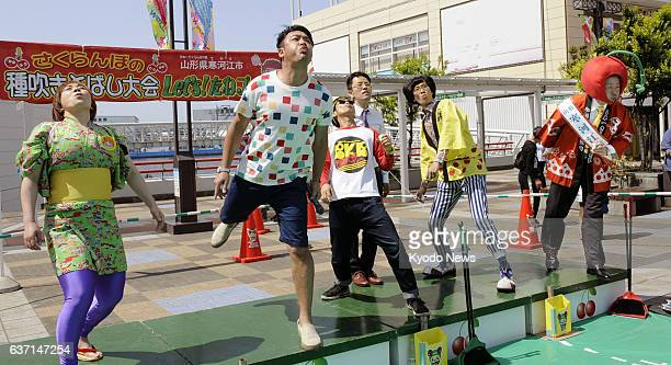 OSAKA Japan Comedian Kenji Tamura and other people compete in a cherry pitspitting contest in Osaka western Japan on May 10 2014 On the extreme right...
