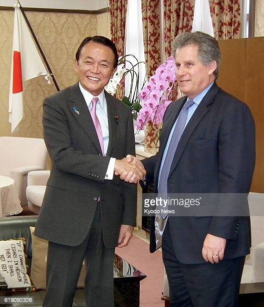 TOKYO Japan David Lipton first deputy managing director of the International Monetary Fund and Japanese Finance Minister Taro Aso shake hands at the...