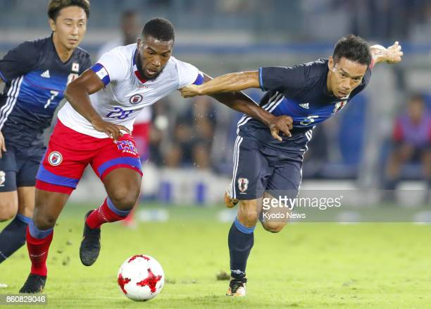 Japan defender Yuto Nagatomo vies for the ball against Haiti forward Duckens Nazon during a friendly match at Nissan Stadium in Yokohama on Oct 10...