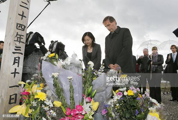 SENDAI Japan Dieter Flury a member of the Vienna Philharmonic bows his head after offering flowers at a monument honoring victims on Mt Hiyori in...