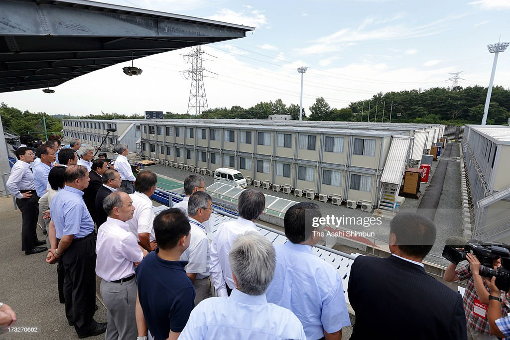 Japan Football Association (JFA) executive committee members inspect temporary housing set up at former main stadium for Tokyo Electric Power Co staffs at J.Village, JFA's national training center on July 11, 2013 in Hirono, Fukushima, Japan. J.Village, only 20 kilometers away from the Fukushima Daiichi Nuclear Power Plant, has been acting as the frontline base for 3,000 workers of the crippled plant stabilization. JFA is to make a plan to restore the facility as national training center after some of nulcear disaster restoration functions are now relocated to closer site of the plant.