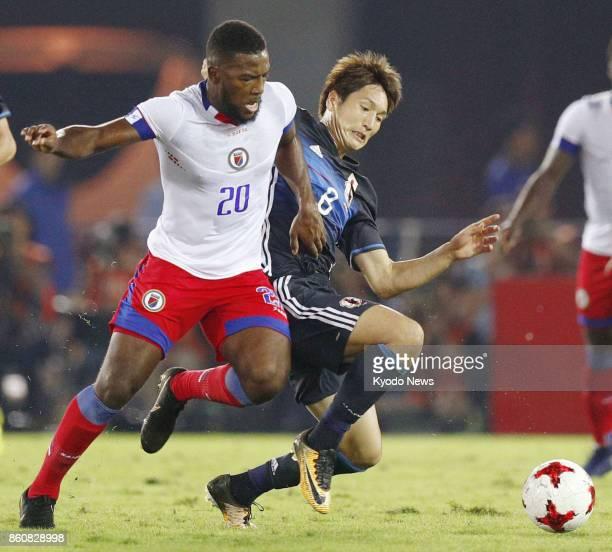 Japan forward Genki Haraguchi vies for the ball against Haiti forward Duckens Nazon during a friendly match at Nissan Stadium in Yokohama on Oct 10...