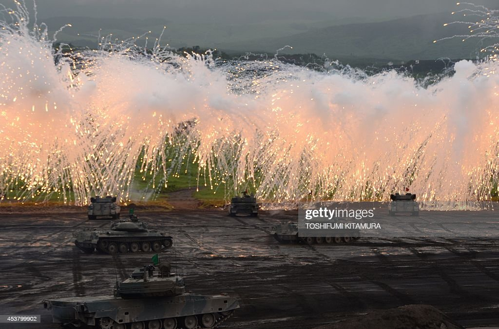 Japan Ground Self Defense Forces' tanks and armoured vehicles move underneath the umbrellas of curtain fires during an exercise in its Higashi-Fuji training ground in Gotemba, some 100 kilometre west of Tokyo on August 19, 2014. A total of 2,300 personnels, 80 tanks and armoured vehicles, 20 aircrafts and 600 vehicles participated in the exercise.