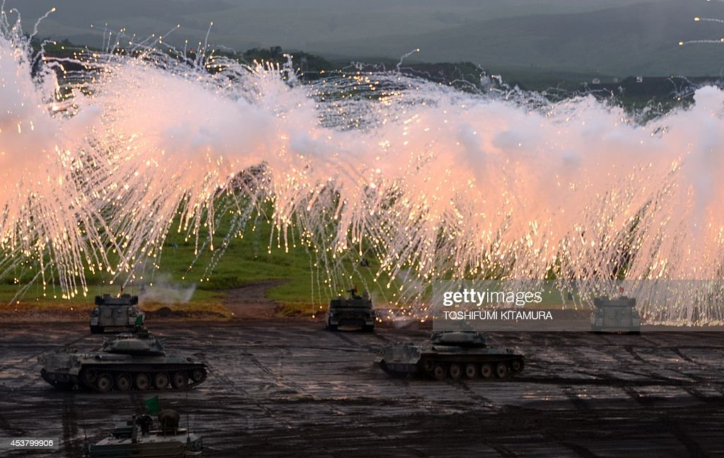 Japan Ground Self Defense Forces' tanks and armoured vehicles move underneath the umbrellas of curtain fires during an exercise in its Higashi-Fuji training ground in Gotemba, some 100 kilometre west of Tokyo on August 19, 2014. A total of 2,300 personnels, 80 tanks and armoured vehicles, 20 aircrafts and 600 vehicles participated in the exercise. AFP PHOTO / TOSHIFUMI KITAMURA