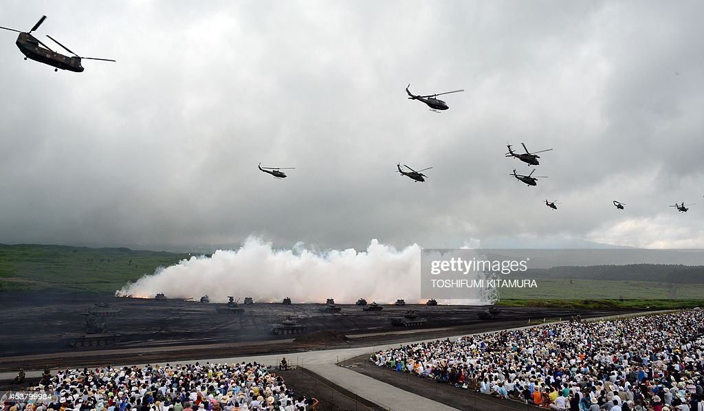 Japan Ground Self Defense Forces' tanks and armoured vehicles move underneath the umbrellas of curtain fires while helicopters fly by during an exercise in its Higashi-Fuji training ground in Gotemba, some 100 kilometre west of Tokyo on August 19, 2014. A total of 2,300 personnels, 80 tanks and armoured vehicles, 20 aircrafts and 600 vehicles participated in the exercise.