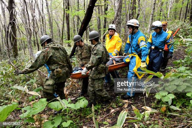 Japan Ground SelfDefense Force members and Police officers carry a stretcher from the crash site of the Japan Ground SelfDefense Force LR2...