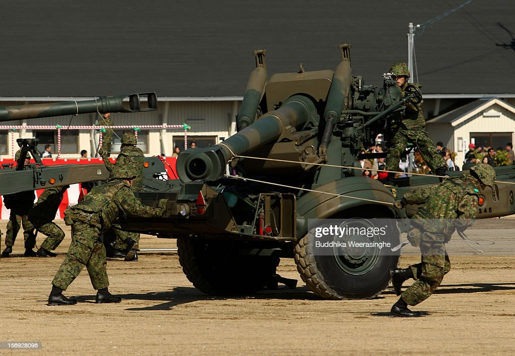 Japan Ground Self-Defense Force (JGSDF) officers pull a Towed FH70 artillery gun during the annual military demonstration on November 25, 2012 in Himeji, Japan. The military exhibition and demonstration marks the 61-year anniversary of the Japan Ground Self-Defense Force based in Himeji.