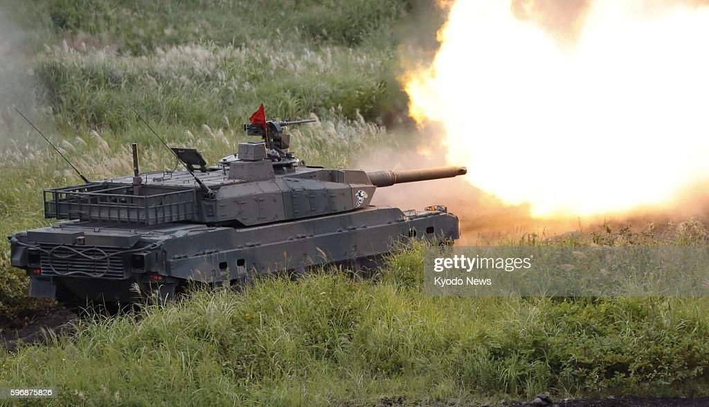 A Japan Ground SelfDefense Force Type 10 armored tank fires during an annual livefire exercise at the HigashiFuji training range at the foot of Mt...