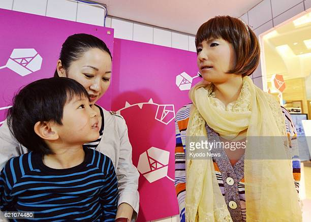 OSAKA Japan Guests chat with a robot resembling a woman at Takashimaya department store in Osaka on May 1 2013 The humanoid developed jointly by...