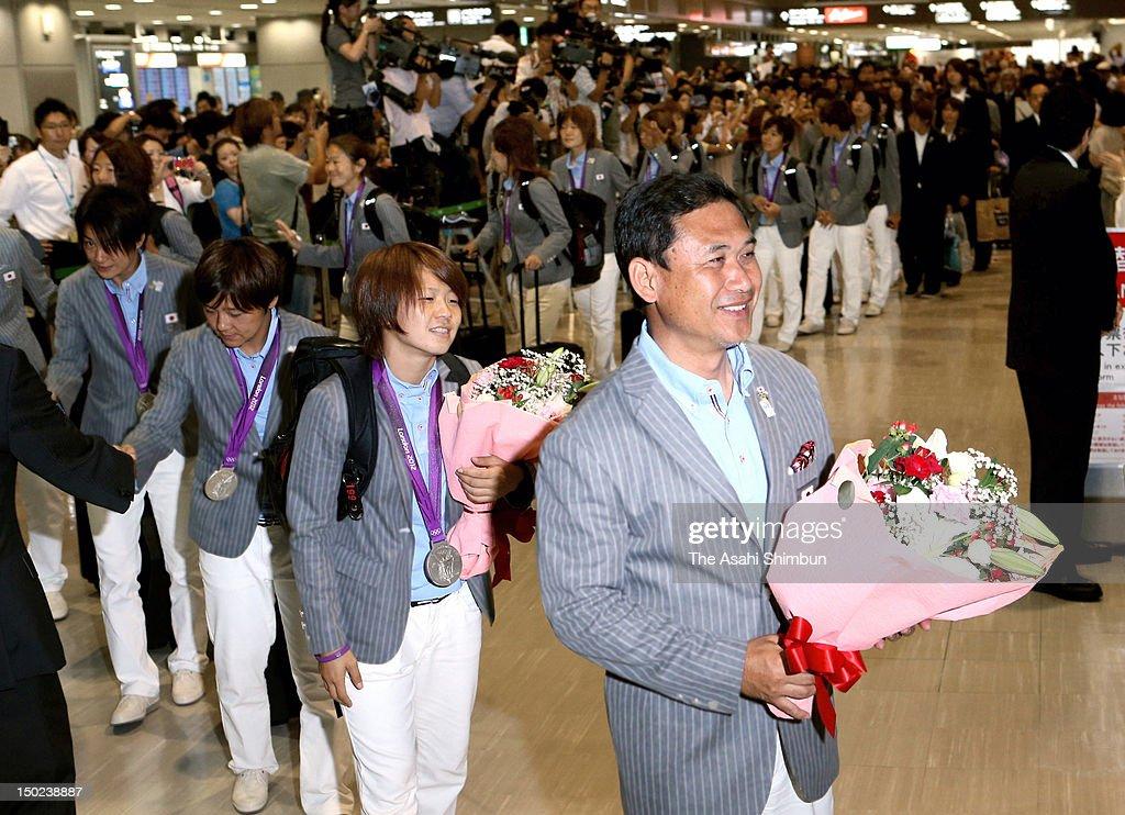 Japan head coach Norio Sasaki (1R) and captain Aya Miyama and Japan Women's football team members are seen upon arrival at Narita International Airport on August 11, 2012 in Narita, Chiba, Japan.