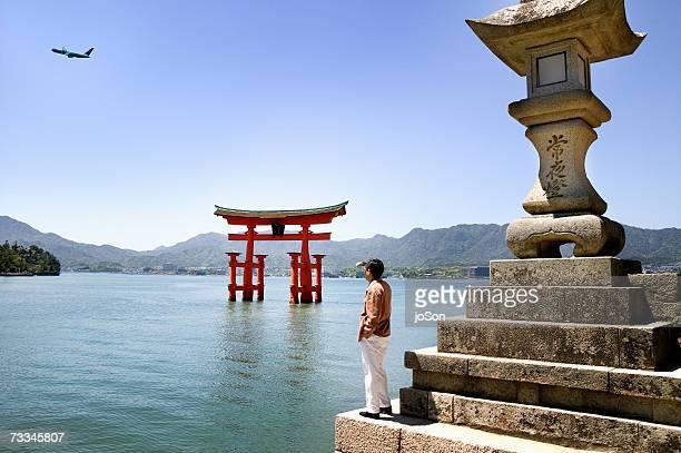 Japan, Honshu , Chugoku Region, Hiroshima, Setonaikai National Park, man looking at plane, rear view