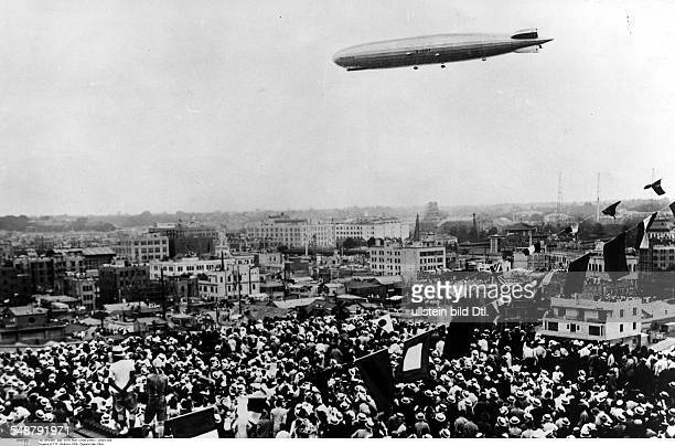 Japan Honshu Tokyo Roundtheworld voyage of the Graf Zeppelin the Zeppelin over Tokyo watched by people on the roofs 1929 Vintage property of ullstein...