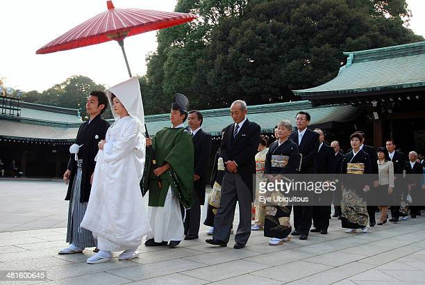 Japan Honshu Tokyo Yoyogi Meiji Jingu shrine a wedding party in procession bride in traditional white wedding kimono in front with groom in...