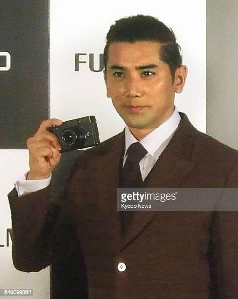 TOKYO Japan Japanese actor Masahiro Motoki holds Fujifuilm Corp's compact camera ''Fujifilm X10'' in Tokyo on Oct 5 2011 The X10 featuring an ultra...