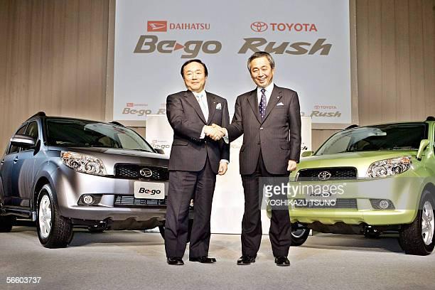 Japanese automaker Daihatsu President Teruyuki Minoura shakes hands with Toyota Motor executive Yoichiro Ichimaru as they intoduce the new compact...