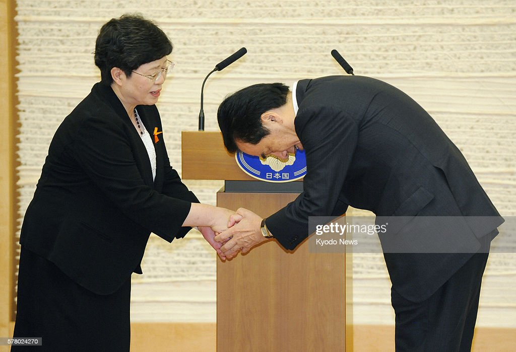TOKYO Japan Japanese Prime Minister Naoto Kan apologizes to Mieko Taniguchi the leader of plaintiffs in damages suits brought against the state over...