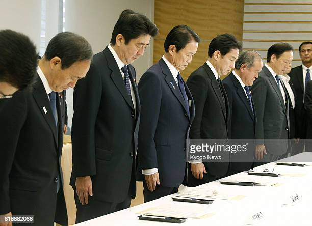TOKYO Japan Japanese Prime Minister Shinzo Abe and other attendees observe a moment of silence at the outset of a meeting of the government's task...