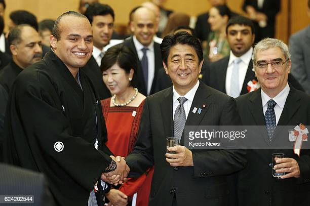 TOKYO Japan Japanese Prime Minister Shinzo Abe shake hands with Egyptian sumo wrestler Osunaarashi as the premier hosted 'Iftar' a Muslim...