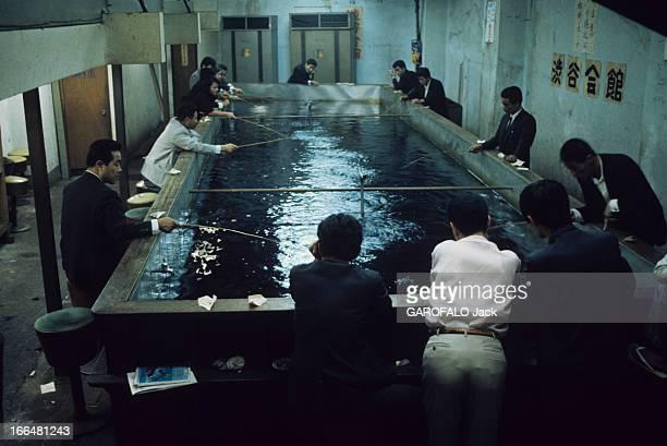 Japan Japon novembre 1968 des hommes se sont regroupés autour d'un bassin de pisciculture et semblent pêcher