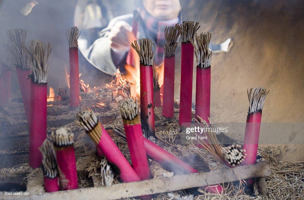 Japan, Kamakura, woman lighting incense sticks : Stock Photo