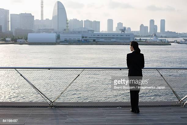 Japan, Kanagawa Prefecture, Yokohama City, Business woman standing by river, skyline in background, rear view