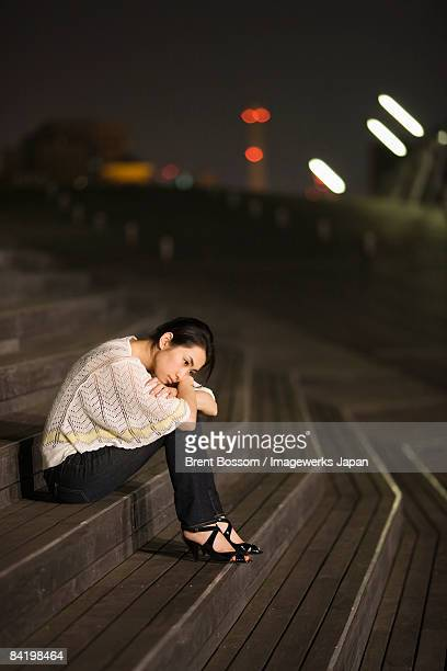 Japan, Kanagawa Prefecture, Yokohama City, Young woman sitting on steps at night, side view