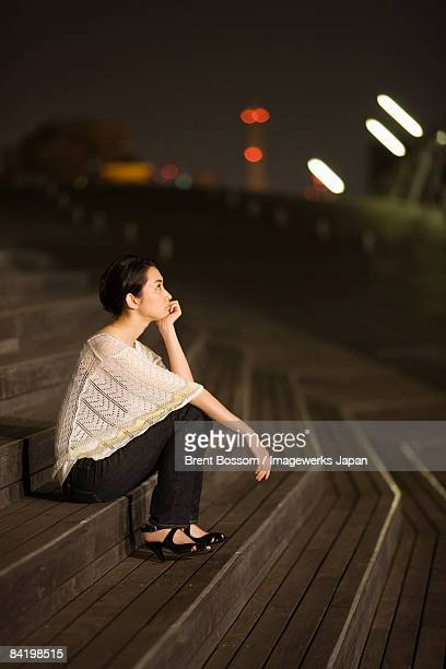 Japan, Kanagawa Prefecture, Yokohama City, Young woman sitting on steps with head in hands at night, side view