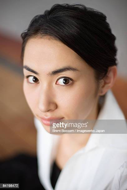 Japan, Kanagawa Prefecture, Yokohama City, Young woman staring, portrait, close-up