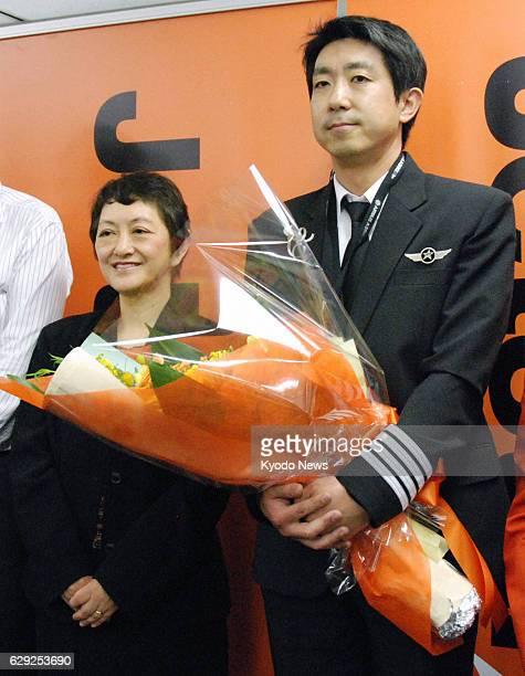 NARITA Japan Kuniyasu Mitsuhashi holds a bunch of flowers presented to him at Tokyo's Haneda airport after his debut flight as the first internally...