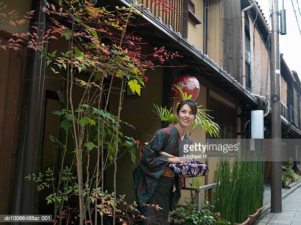 Japan, Kyoto, Gion, woman in kimono waiting with wrapped gift in street