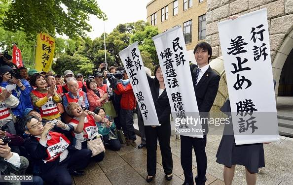 YOKOHAMA Japan Lawyers hold banners before plaintiffs in front of the Yokohama District Court in Kanagawa Prefecture on May 21 after the court...