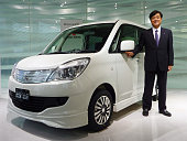 TOKYO Japan Masuko Osamu president of Mitsubishi Motors Corp poses with the Delica D2 to be launched in March The compact minivan features a...