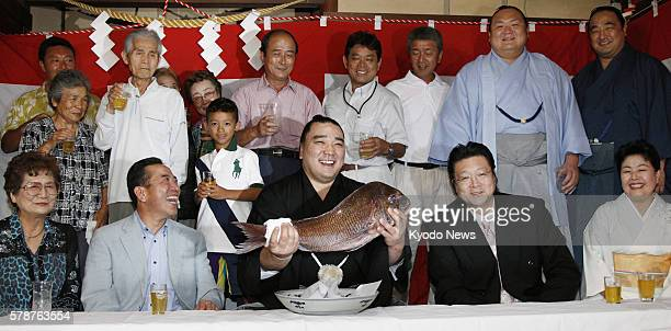 NAGOYA Japan Mongolian ozeki Harumafuji surrounded by his fellow Isegahama Stable wrestlers and their supporters lifts a sea bream an auspicious fish...