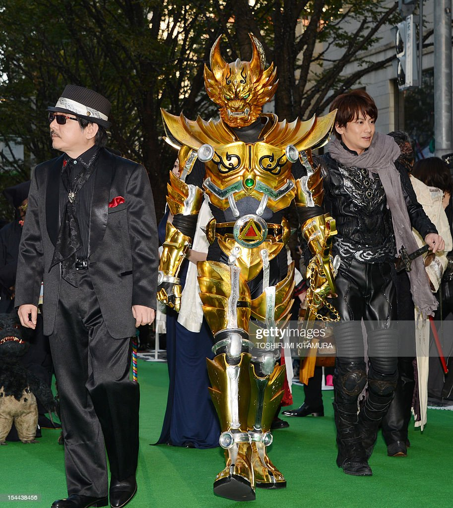 Japan movie, 'Garo and The Wailing Dragon' director Keita Amemiya (L), a person dressed as character Garo (C) and actor Yuki Kubota (R) walk on the carpet during the Tokyo International Film Festival (TIFF) opening ceremony in Tokyo on October 20, 2012. With China's main entry to the film festival being pulled, a total of 103 movies will be screened during the nine-day event.