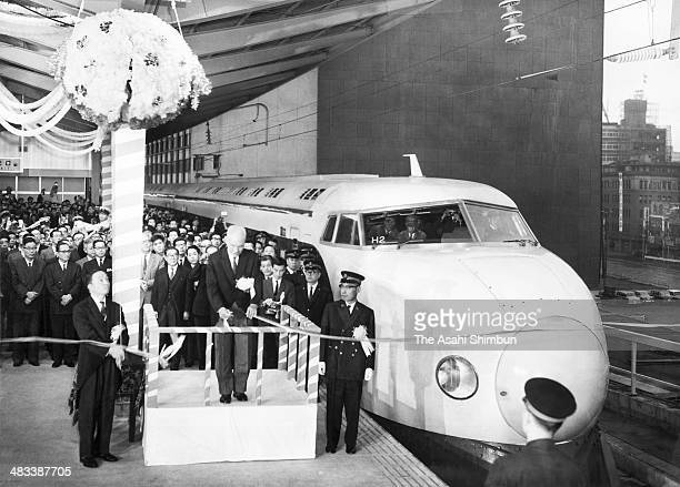 Japan National Railways President Reisuke Ishida cuts a tape during the ceremony to launch the Shinkansen bullet train between Tokyo and Shin Osaka...