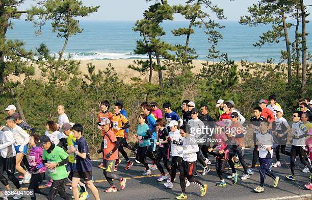 TOTTORI Japan Participants of the Tottori marathon run along a road next to the Tottori sand dunes on the coast of the Sea of Japan on March 16 2014