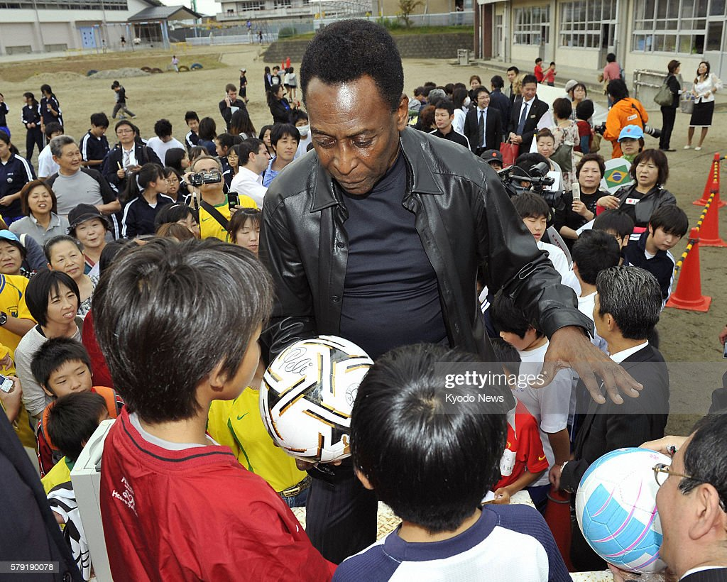 NATORI Japan Pele the legendary Brazilian footballer called ''the king of football'' hands an autographed soccer ball to children at an elementary...