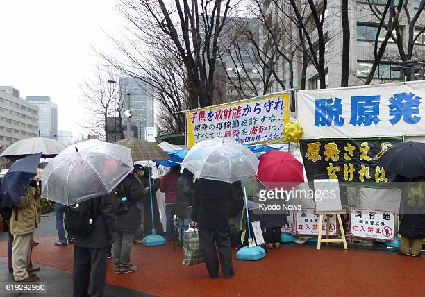 TOKYO Japan People have their umbrellas up as they look on at an hourlong live program under rain at 'Tent Square' on Feb 15 in Tokyo's Kasumigaseki...