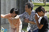ITOMAN Japan People search the names of the deceased on the Cornerstone of Peace monument black granite tablets inscribed with the names of the...